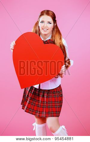 Pretty smiling teen girl in school plaid skirt and white blouse posing over pink background with big red heart. Anime style.