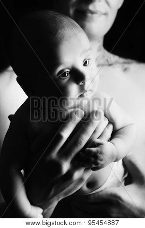 Lovely little baby on the father's hands. Safety and care concept. Happy childhood. Studio shot over black background.