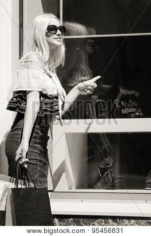 Fashion blond woman with shopping bags at the mall window