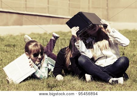 Group of happy teenage school girls lying on a grass in campus