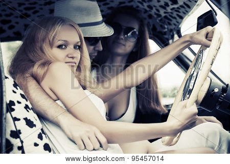 Young fashion people driving retro car