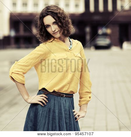 Happy young fashion woman with curly hairs on a city street