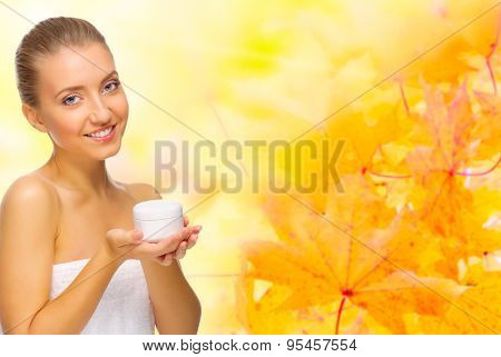 Healthy girl with body cream jar on autumnal background