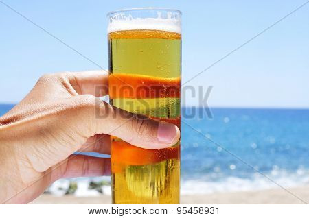 closeup of a young caucasian man having a refreshing beer on the beach
