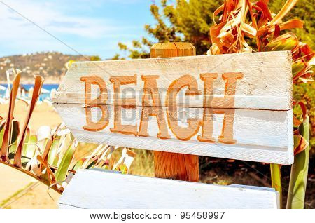 closeup of a wooden signpost with the text beach written in it, in Ibiza Island, Spain, with a filter effect