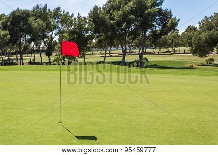 Red flag in the hole on a green golf field