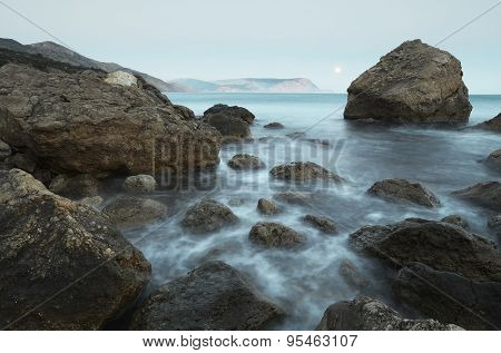 Morning landscape with the sea and rocks on the shore. Full moon in the sky