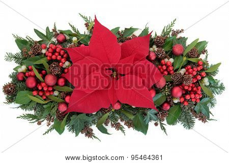 Thanksgiving and christmas poinsettia flower display with red baubles, holly, winter greenery and red bauble decorations over white background.