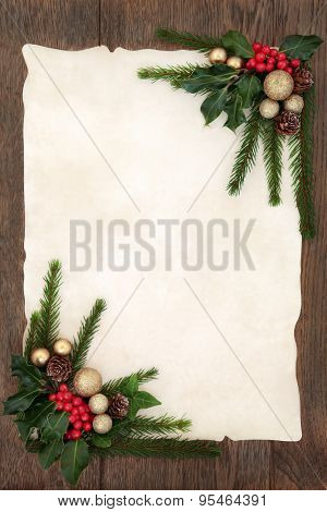 Christmas background floral border with gold bauble decorations, holly, ivy, fir and pine cones on parchment paper over old oak wood.