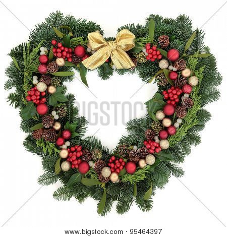Christmas heart shaped wreath with baubles, gold ribbon bow, holly, mistletoe and winter greenery over white background.