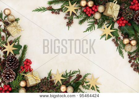 Christmas background border with gold bauble decorations, holly, mistletoe, fir and cedar cypress greenery on old parchment paper.