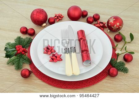Christmas dinner place setting with plates, antique cutlery, red baubles, cracker, holly, mistletoe and fir over light oak background.