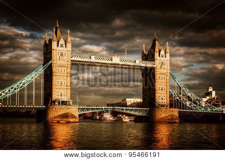 Tower Bridge in London, the UK. Dramatic stormy and rainy clouds with sunset sun shining. One of the symbol of England, Great Britain