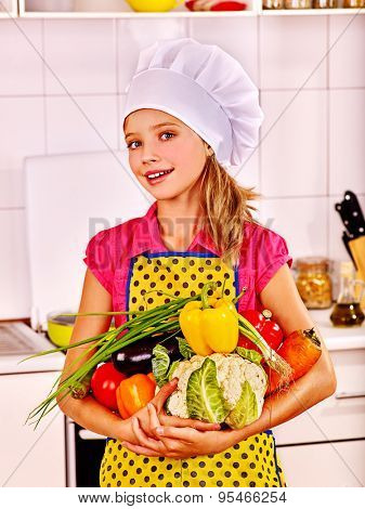 Teenager girl holding vegetable at kitchen.