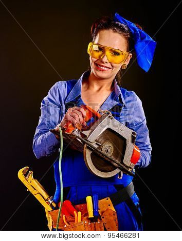 Happy woman builder in mask with circular saw on black background.