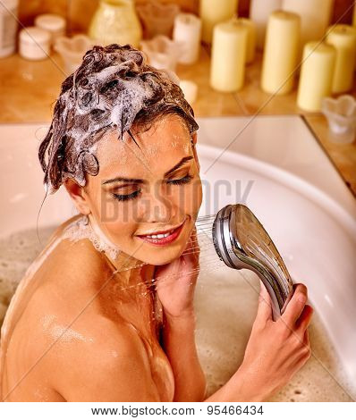 Young woman with wet head take bubble  bath.