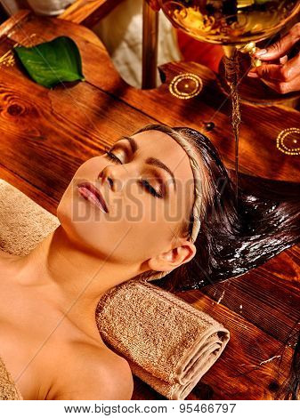 Young woman lying on back having oil Ayurveda spa treatment.