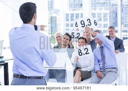 Smiling business team showing paper with rating in the office