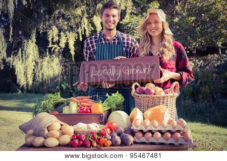 Happy farmers standing at their stall on a sunny day