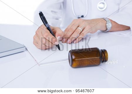 Doctor writing on a notepad in medical office