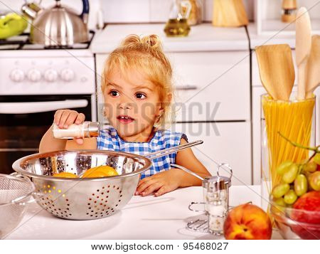 Alone child in blue home dress with rolling-pin dough at home kitchen.