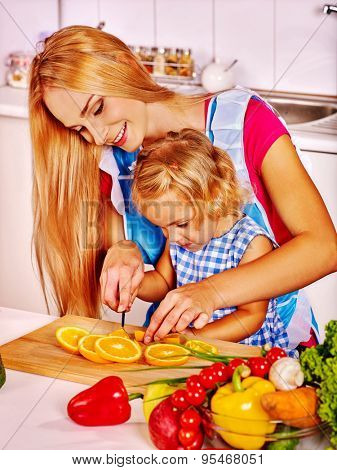 Mother and daughter prepare food and cut orange at kitchen.