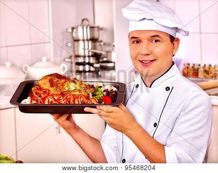 Happy man in chef hat taking cooking chicken.