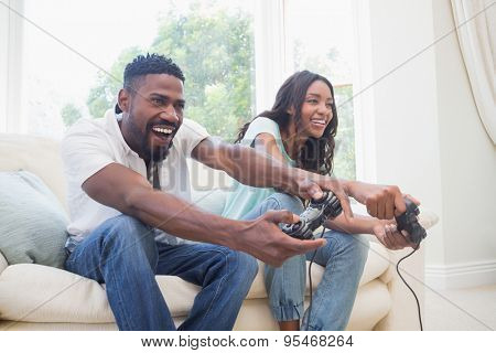 Happy couple on the couch playing video games at home in the living room