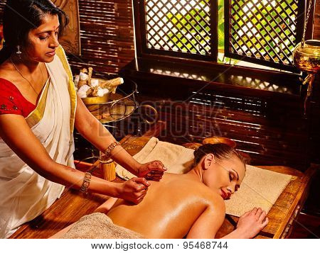 Young woman lying on stomach having oil Ayurveda spa treatment.