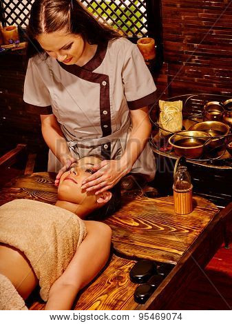 Couple  having oil facial spa treatment in wooden salon.