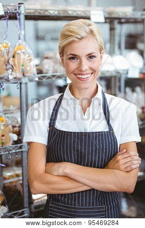 Selfassured female cook smiling in front of her bakery