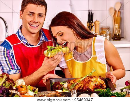 Couple cooking chicken and eating hot dog at kitchen.Woman is feeding man