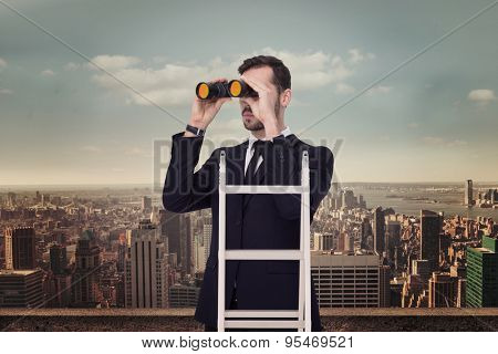 Businessman looking on a ladder against balcony overlooking city