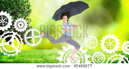 Happy classy businesswoman jumping while holding umbrella against field against glowing lights