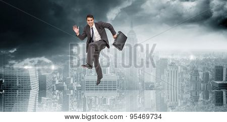 Happy businessman in a hurry against room with large window looking on city