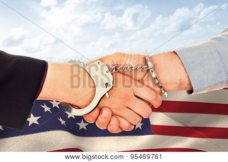 Business people in handcuffs shaking hands against blue sky