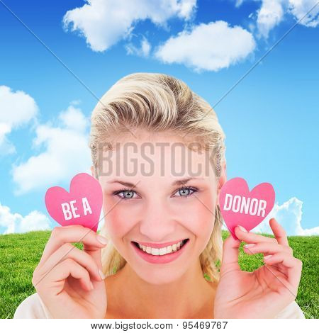 Attractive young blonde holding little hearts against blue sky over green field