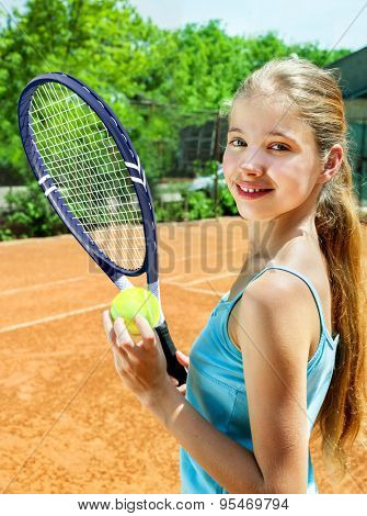 Happy child girl holding  racket and ball on  brown tennis court. Green tree on background.
