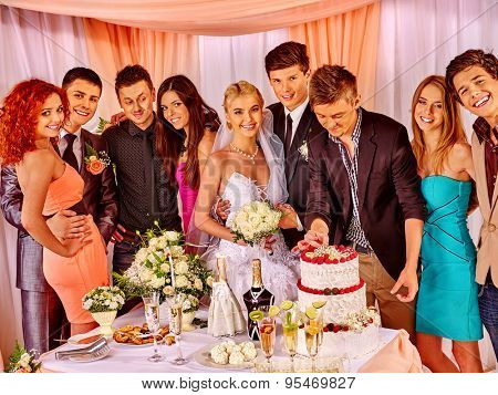 Group people at wedding table with cake. Groom and bride.
