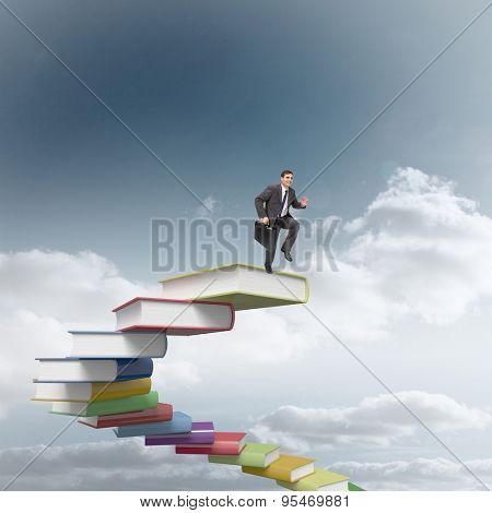 Cheerful businessman in a hurry against stack of books