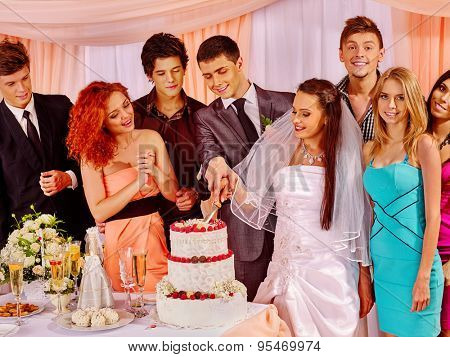Group people at wedding table with cake in blanket room.