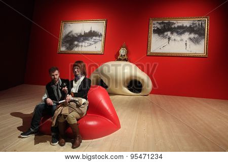 PARIS, FRANCE - JANUARY 7, 2013: Visitors take a picture as they sit at the Mae West Lips Sofa by Salvador Dali displayed at his retrospective exhibition in Paris, France.