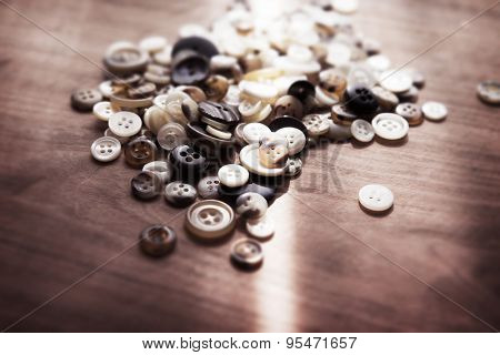 Buttons on a old work table with ray of window light. Shallow depth of field. Intentionally shot in retro tone.