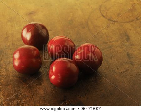 Fresh harvested plums, very ripe Plums on a old wooden table. Low key.