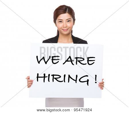 Young businesswoman holding a placard showing with we are hiring phrases