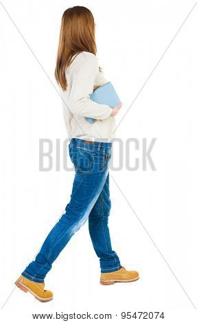 Girl comes with  stack of books.back view. Rear view people collection.  backside view of person.  Isolated over white background. Girl in a white jacket bears a blue book