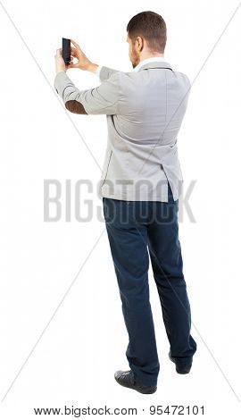 back view of business man on phone photographs. rear view people collection. Isolated over white background. backside view of person.  guy worth photographing everything around him.
