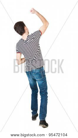 Back view of  man.  Raised his fist up in victory sign.  Rear view people collection.  backside view of person.  Isolated over white background. guy in striped T-shirt showing joy out his hand forward