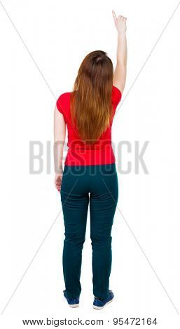 Back view of  pointing woman. beautiful girl. Rear view people collection.  backside view of person.  Isolated over white background.  Low girl in green trousers shows thumb up.