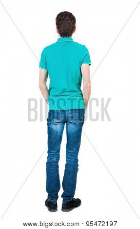 Back view of man in jeans. Standing young guy. Rear view people collection.  backside view of person.  Isolated over white background. The guy in a stylish aquamarine shirt is his hands in his pockets
